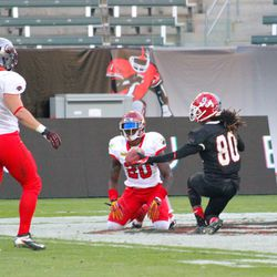 Isaiah Burse offers the ball to Demetrius Wright after making a catch.