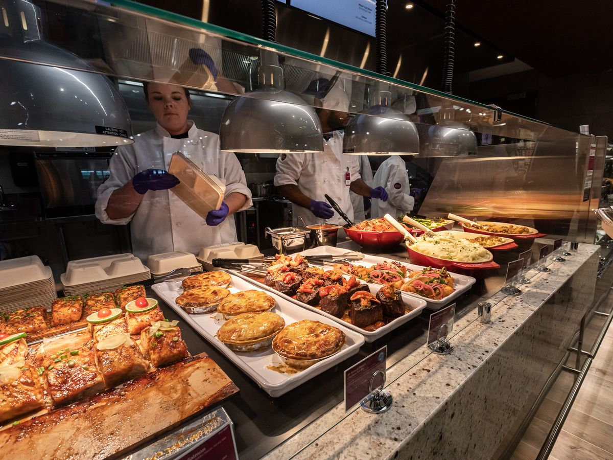 pies, steak, salmon, and other hot prepared foods at the plum market deli counter