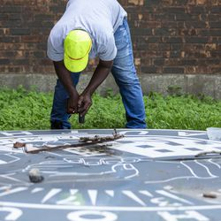 Thomas Taylor, 54, a worker with McKay Landscaping who lives in the North Lawndale neighborhood, works to dismantle and take into storage an old Chicago Housing Authority sign sitting outside the sole remaining building from the Jane Addams Homes in the 1300 block of West Taylor Street, Wednesday, Aug. 21, 2019. The sign once hung at the Robert Taylor Homes, but there are no immediate plans for its restoration or display after years of neglect.