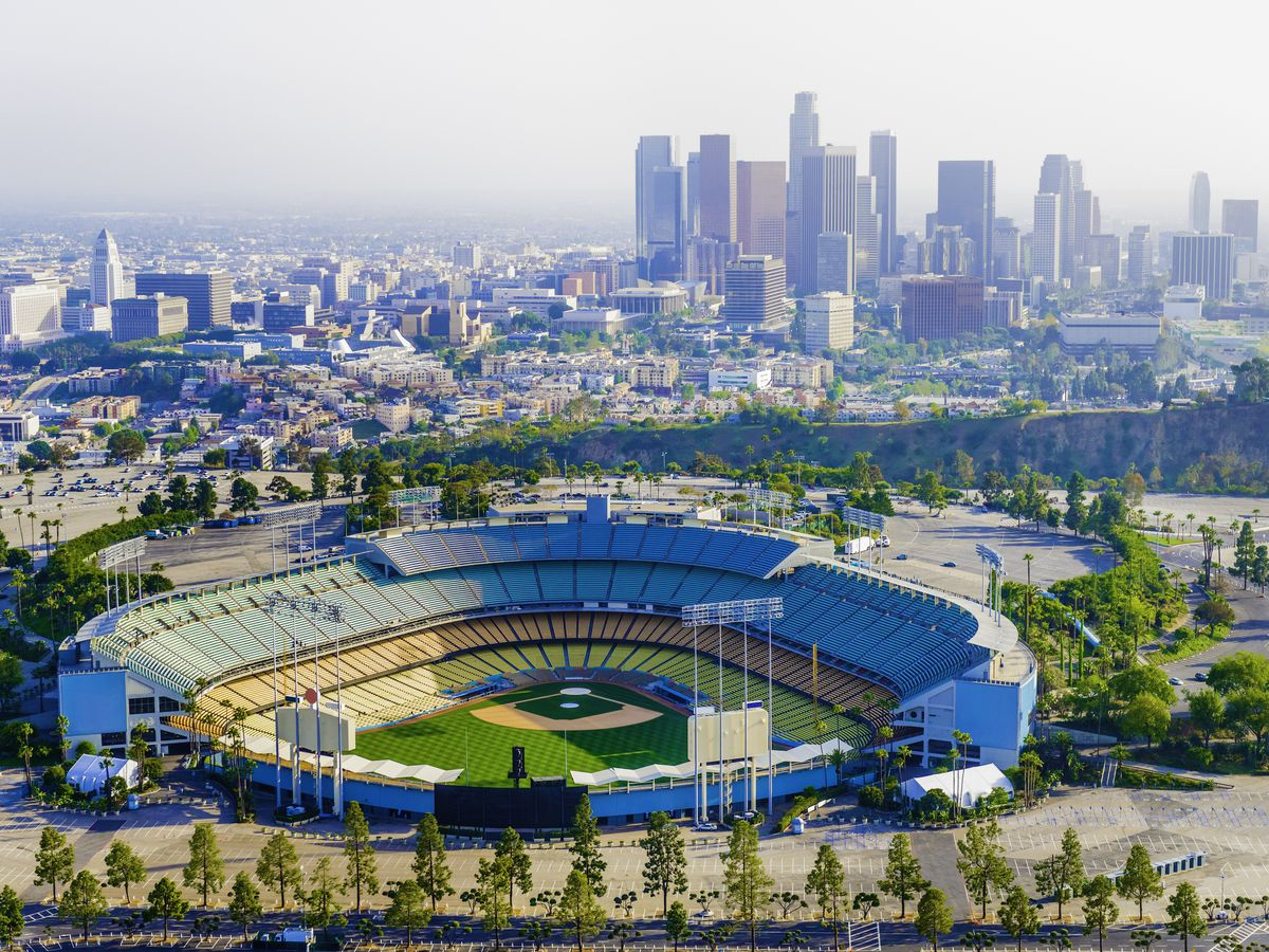 In the foreground is a sports stadium with a baseball field. The stadium is surrounded by trees and a parking lot. In the distance are many city buildings and tall skyscrapers.