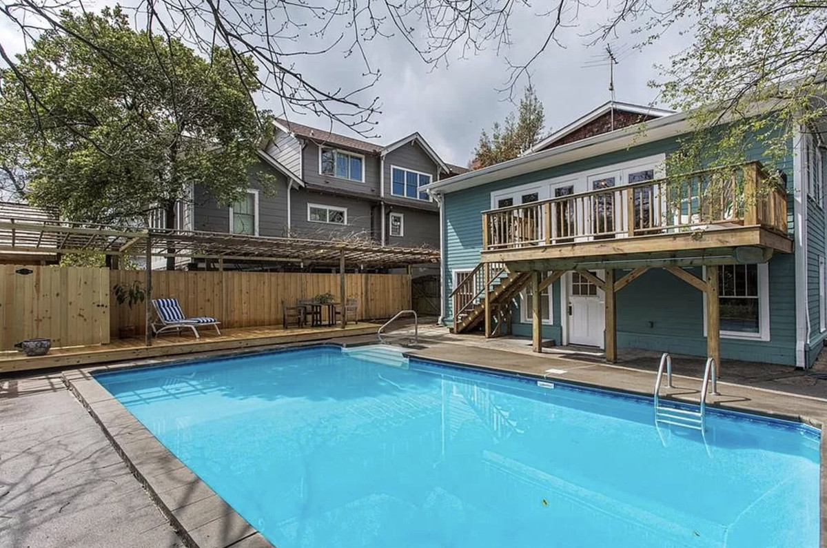 Rear view of house with deck overlooking swimming pool.