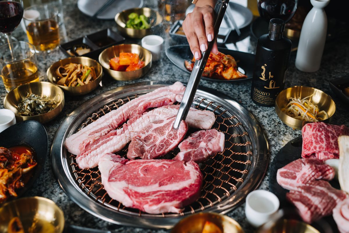 Pork belly, beef, and other meats on the grate of a Korean barbecue table grill. Banchan and other side dishes surround the grill.