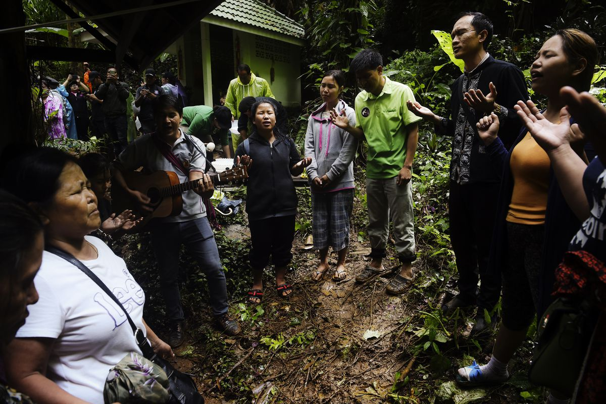 June 27: Relatives pray as they keep vigil near the Tham Luang cave in Chiang Rai, Thailand, while rescue personnel conduct operation for a missing children's football team and their coach. Read More. (Lillian Suwanrumpha/AFP/Getty Images)