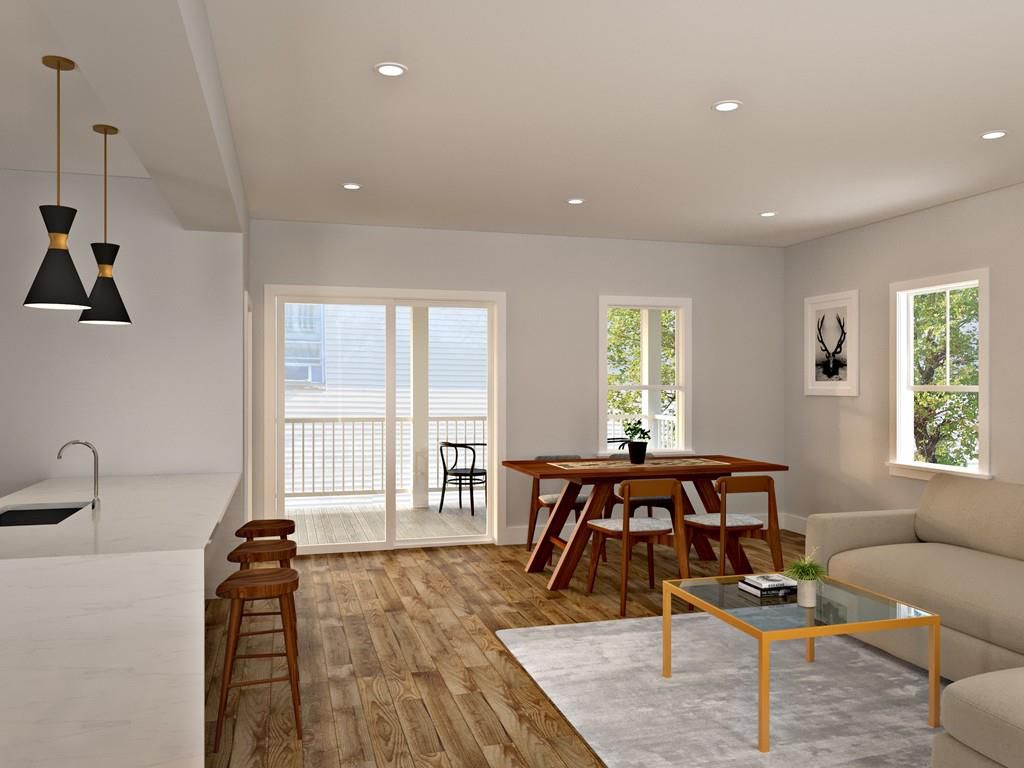 Rendering of a living room and a kitchen, and there's furniture in the living room.