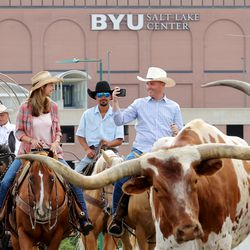 Gov. Spencer Cox, right, takes video as he,first lady Abby Cox and others drive a small herd of Texas longhorn cattle along North Temple toward the Utah State Fairpark in Salt Lake City on Monday, July 19, 2021. The drive was held to celebrate the return of the Days of '47 Cowboy Games and Rodeo.