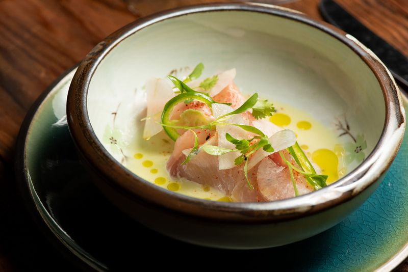 A ceramic bowl holds a raw fish hamachi dish in light oil.