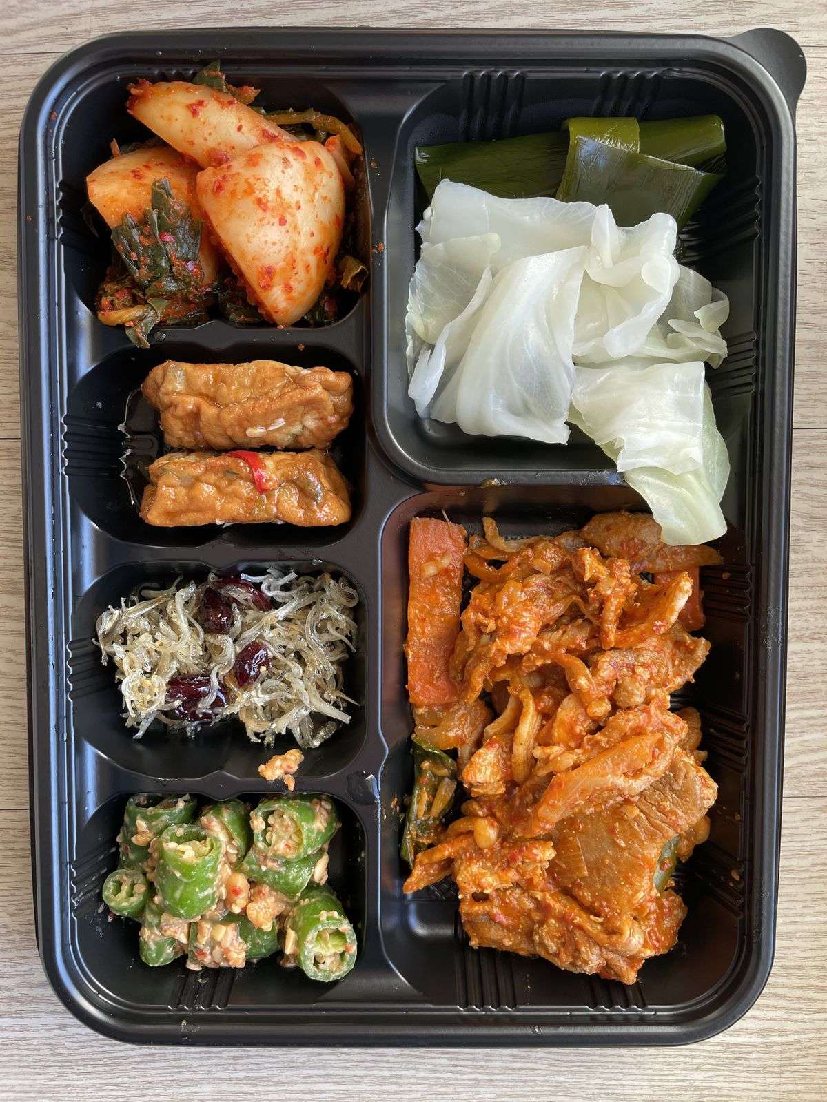 A black container with different Korean foods.