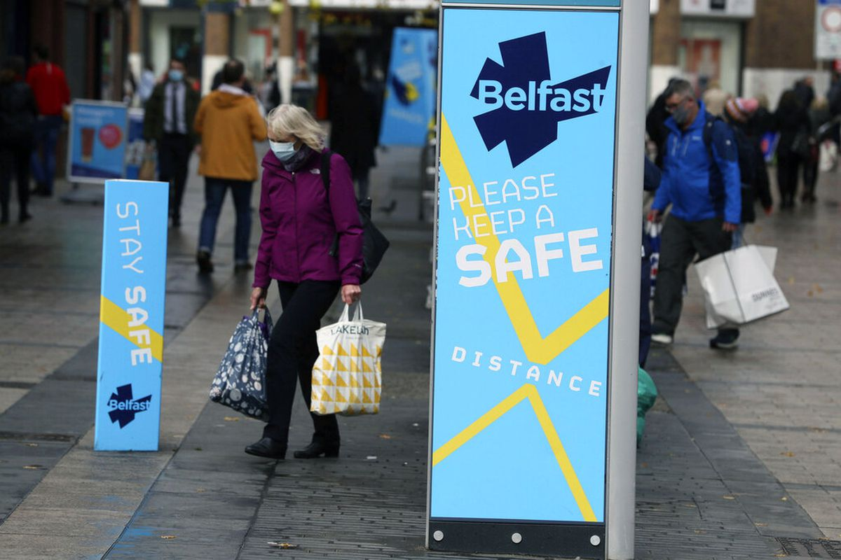 A woman wears a face mask in Belfast city centre, Northern Ireland, Wednesday, Oct. 14, 2020. Northern Ireland introducing the tightest COVID-19 restrictions in the United Kingdom on Wednesday, closing schools for two weeks and pubs and restaurants for a month.