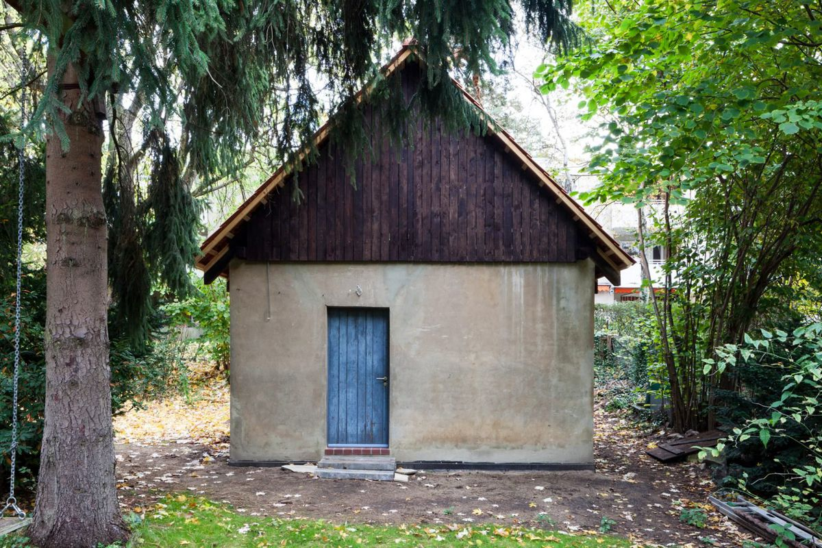 A simple gable structure with tiled roof and concrete body with blue door sits among trees.
