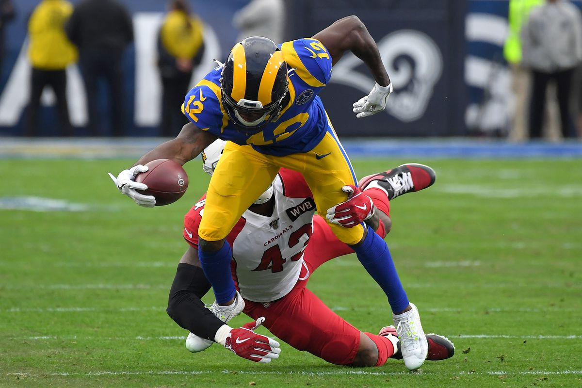 Wide receiver Brandin Cooks of the Los Angeles Rams hangs on to a complete pass before he is stopped by outside linebacker Haason Reddick of the Arizona Cardinals in the second half of the game at the Los Angeles Memorial Coliseum on December 29, 2019 in Los Angeles, California.