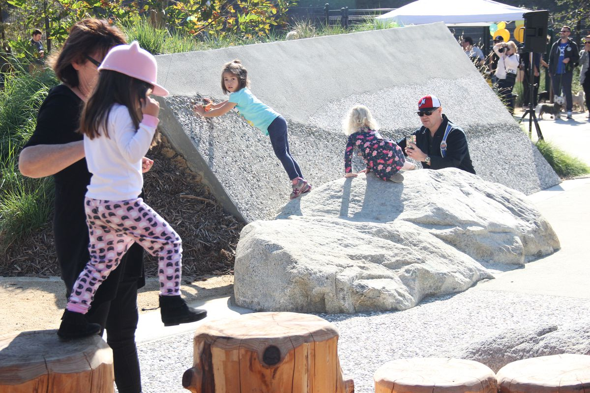 Children climb on rock structures and walk along wooden stumps in a park.