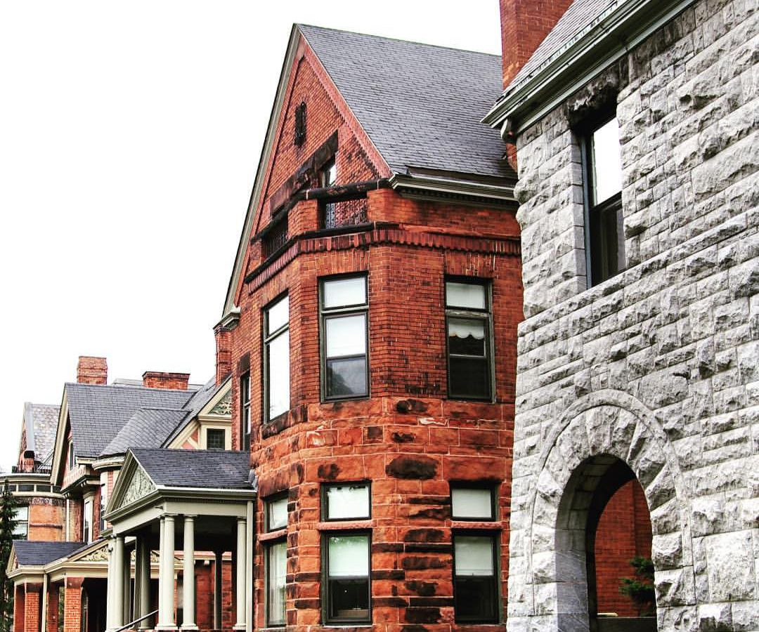 A row of buildings. The building in the foreground is light grey brick. The next building is red brick.