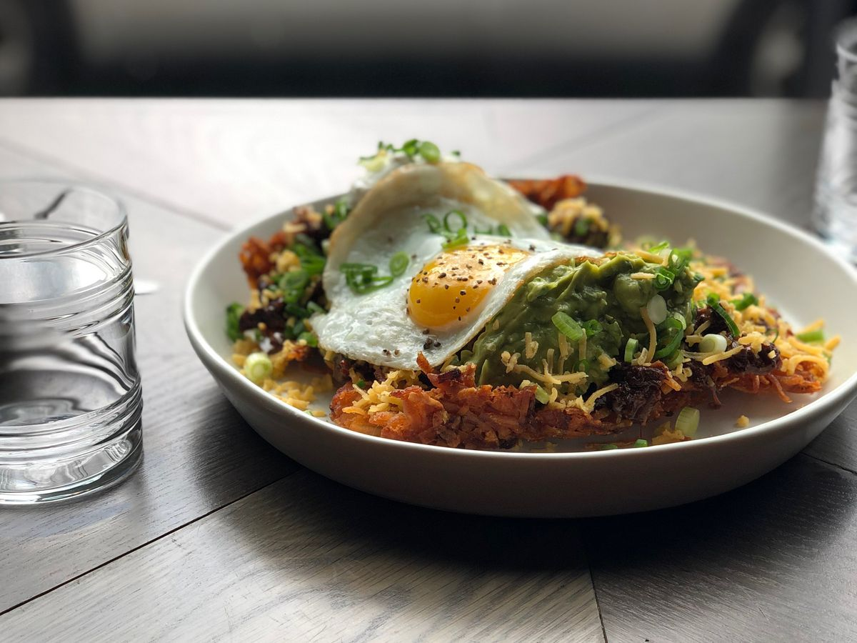An egg-topped hash brown sits in the window of Bullard on a white plate, with shreds of cheese and a hearty dollop of guacamole