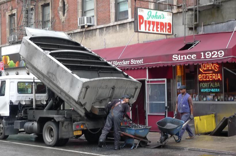 A truck spills coal into a wheel barrow.