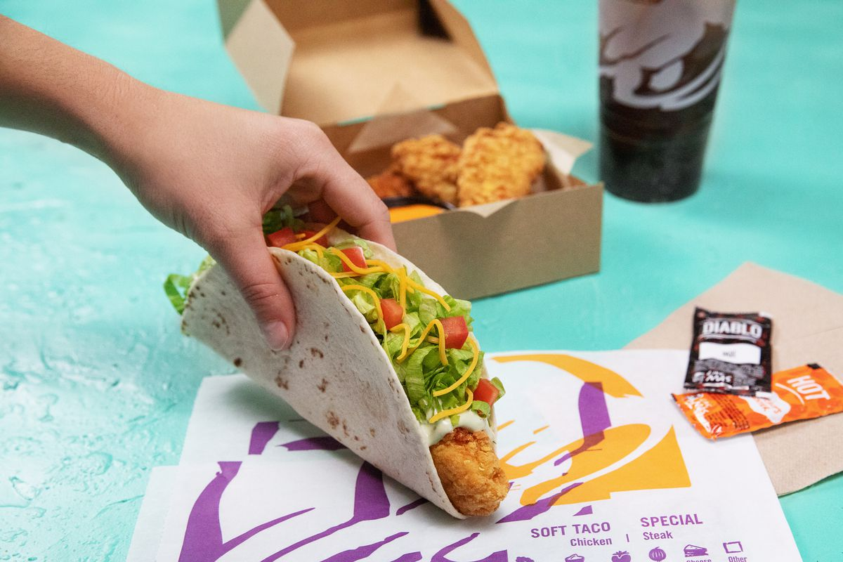 A white hand holding a taco filled with lettuce, tomato, cheese and a fried chicken strip