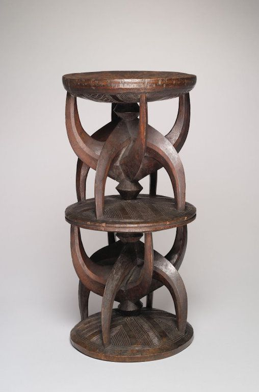 A wooden stool with an elaborate design carved into its base.