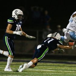 Sky View's Boston Hall (32) hurdles over Ridgeline's Strat Simmons (11) for a first down during a high school football game at Ridgeline High School in Millville on Thursday, Sept. 17, 2020.