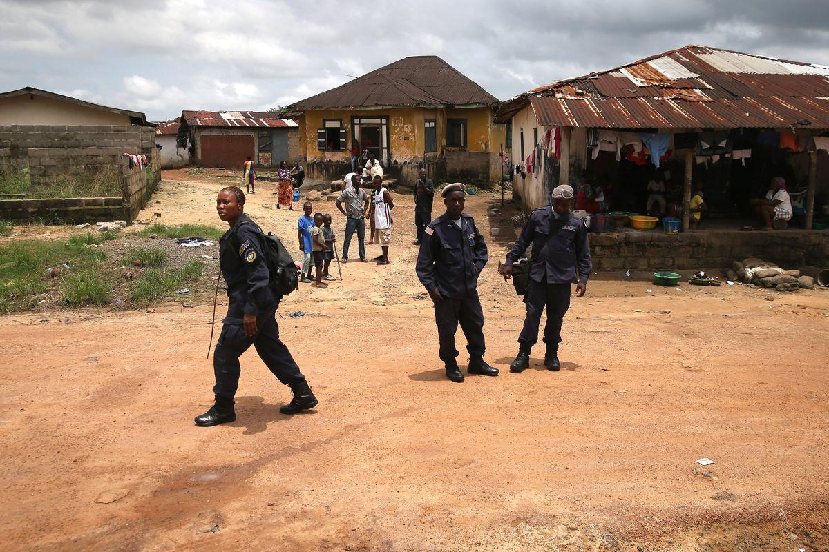 Liberian police enforce a quarantine in Dolo Town, Liberia.