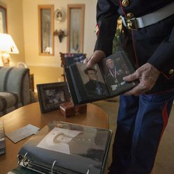 Eighty-seven-year-old retired Marine John Cole, who served and was wounded in North Korea, looks through old photos at his home in Roy Wednesday, Feb. 18, 2015.