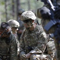 In this photo taken Friday, April 21, 2017 Col. Gregory Beaudoin, center, commander of the 82nd Airborne Division's 3rd Brigade Combat Team, speaks with participates in a training exercise at Fort Bragg, N.C. The Army is planning to triple the amount of bonuses it's paying this year to more than $380 million in a bid to expand its ranks. The money includes new incentives to woo reluctant soldiers to re-enlist.