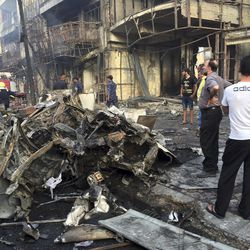 Iraqi security forces and civilians gather at the site after a car bomb at a commercial area in Karada neighborhood, Baghdad, Iraq, Sunday, July 3, 2016. Bombs went off early Sunday in two crowded commercial areas in Baghdad.