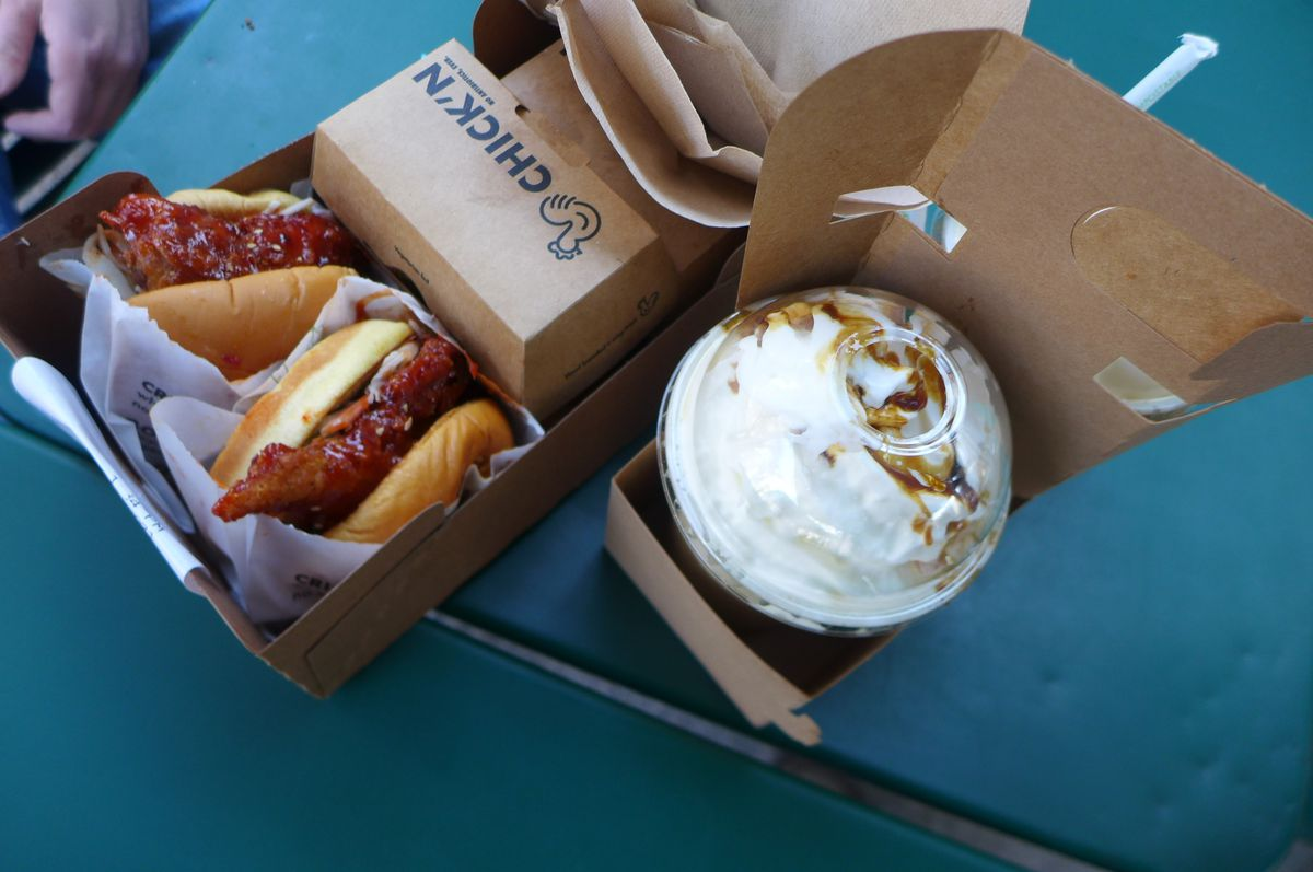 Two chicken sandwiches sticking out of boxes with a dome topped milkshake.