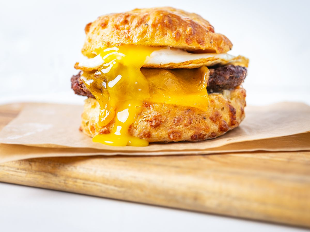 An egg sandwich with sausage oozes yolk onto a cheesy biscuit by Ghost Dog Egg Man