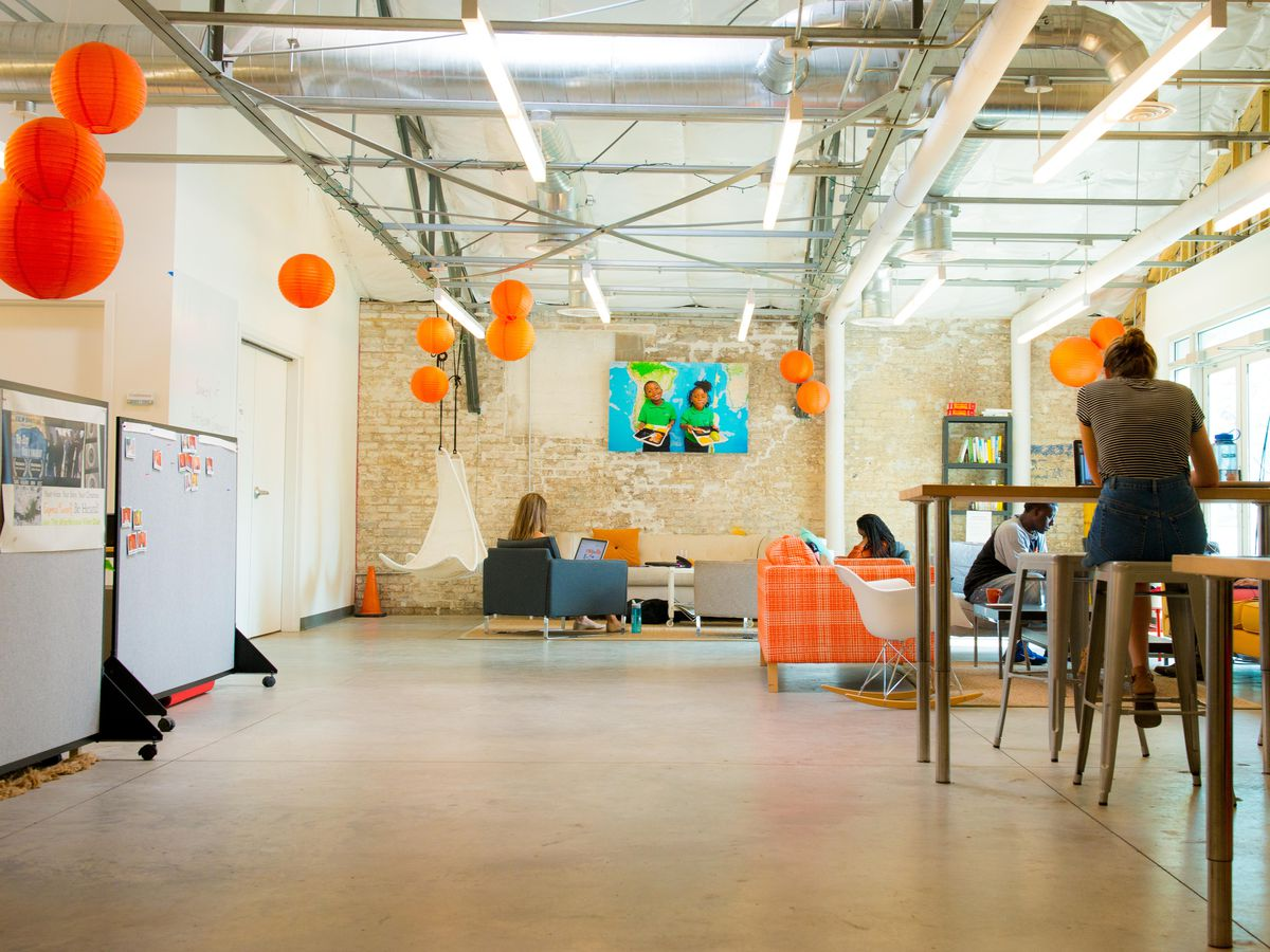 The interior of a co-working space in New Orleans. There are tables and desks.