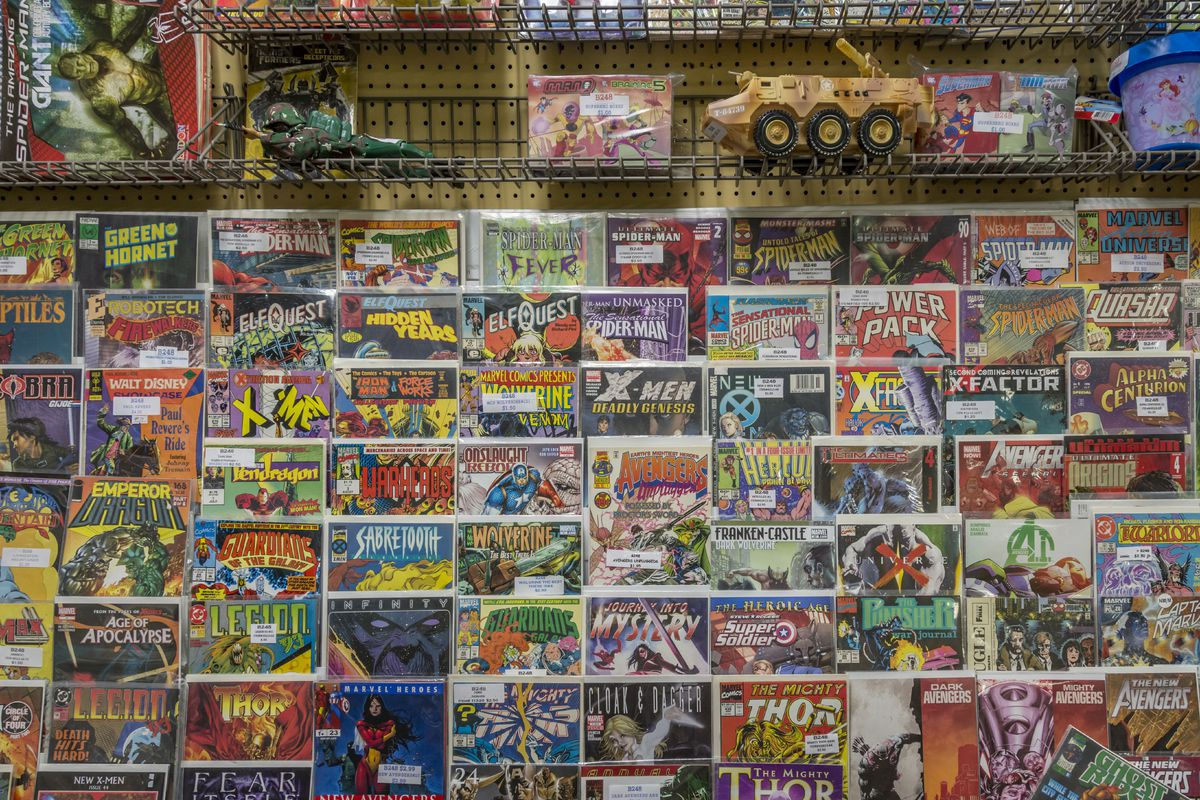Rack of comic books and toys for sale at a flea market