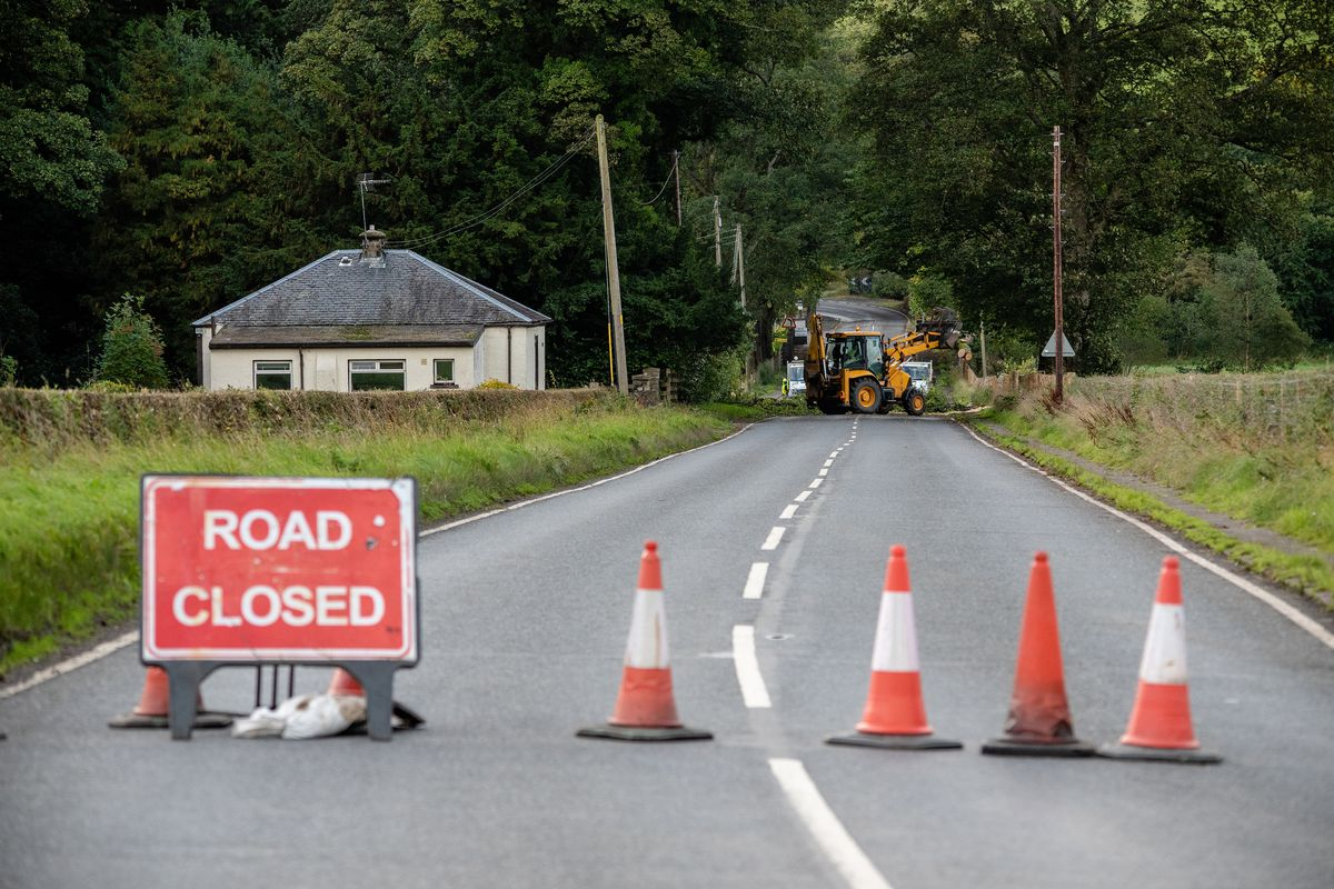 A road closed sign blocks of the road while workers are seen...