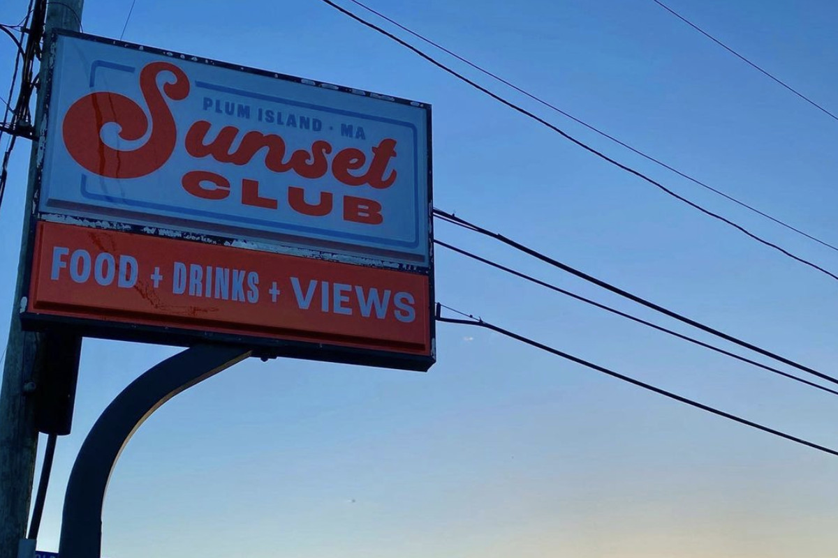 """A white sign with orange text that reads """"Sunset Club: Food + Drinks + Views"""" backdropped by a sunset over a marsh"""