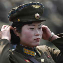 A North Korean female soldier adjusts her hair during a mass meeting of North Korea's ruling party at a stadium in Pyongyang, North Korea, on Saturday April 14, 2012. North Korea will mark the 100-year birth anniversary of the late leader Kim Il Sung on Sunday April 15.