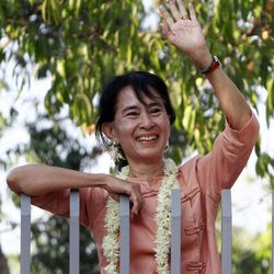 Myanmar pro-democracy leader Aung San Suu Kyi waves to merrymakers from the gate of her lake-side home during the celebration of Thingyan, Myanmar's annual New Year water festival, in Yangon, Myanmar, Monday, April 16, 2012.