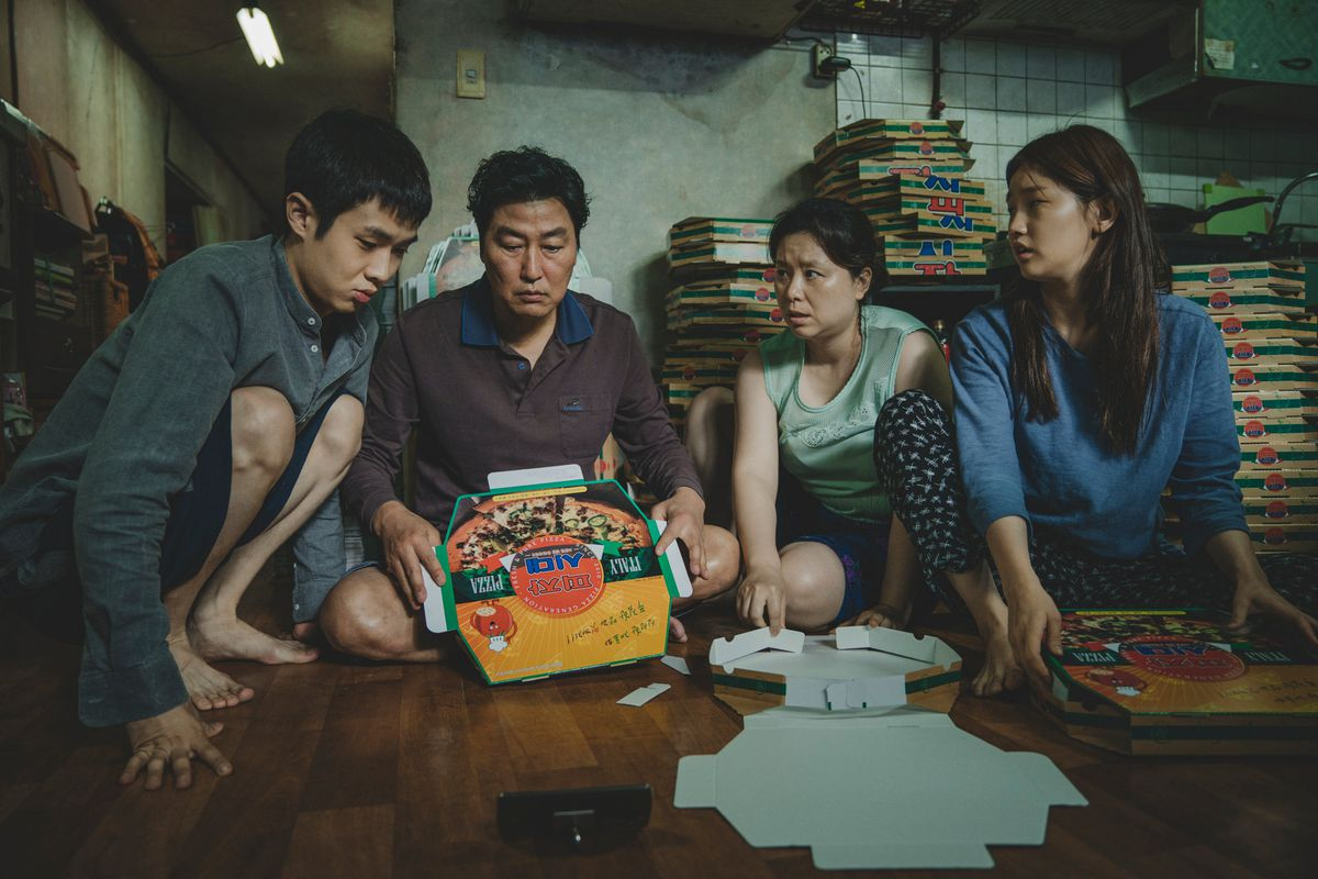 A still from Bong Joon Ho's Parasite, with a family sitting around pizza boxes