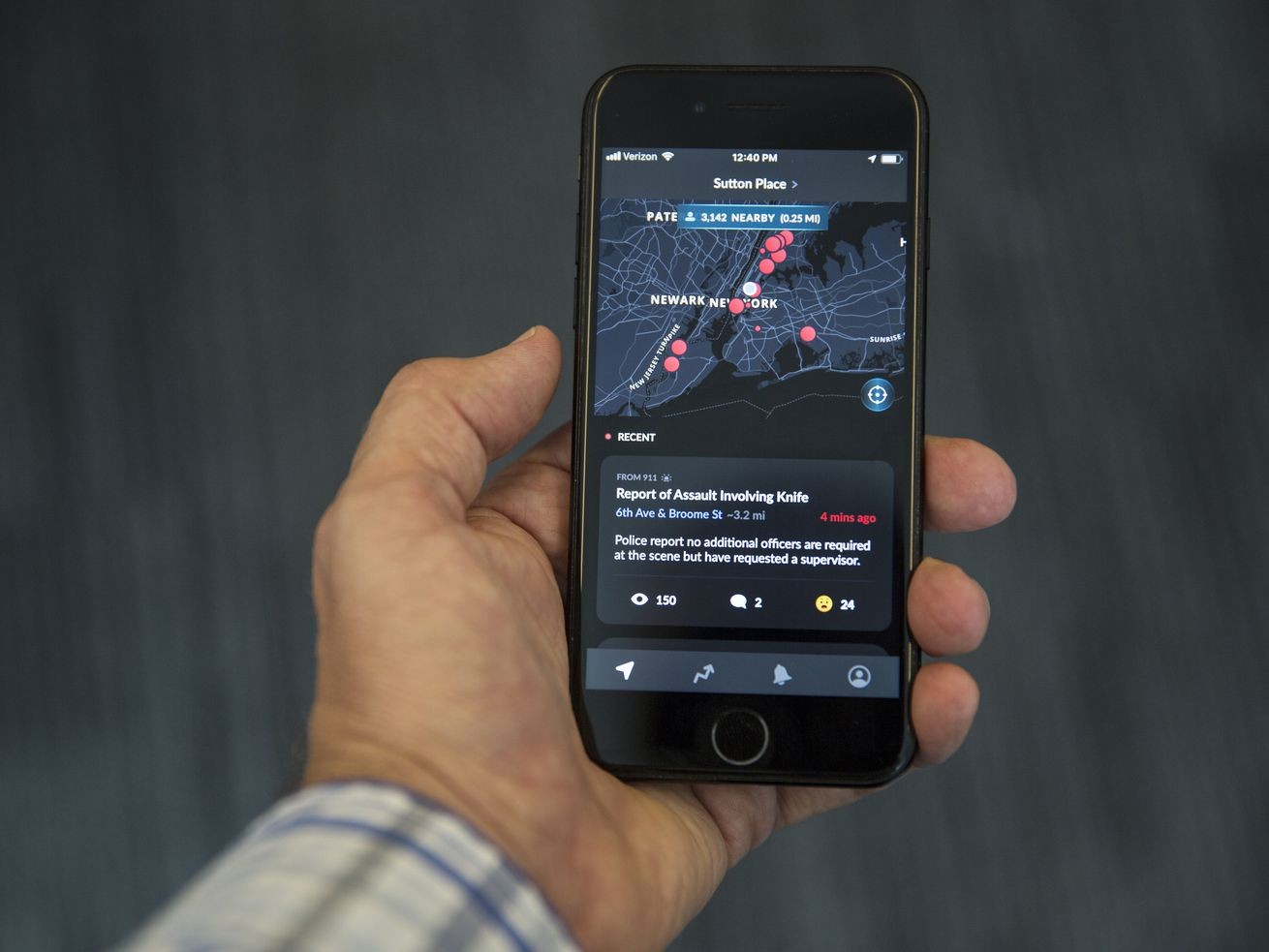 A hand holds an iPhone with the Citizen app on it.