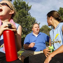 Brad Thomas, middle, who has been coaching his daughter's accelerated softball team for the past five years, talks with Kamryn Henriod during a scrimmage at Dewey Bluth Park in Sandy, Utah, Thursday, June 9, 2016.