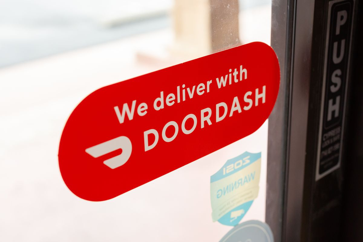 """A red sticker reading """"we deliver with doordash"""" on a clear restaurant door"""