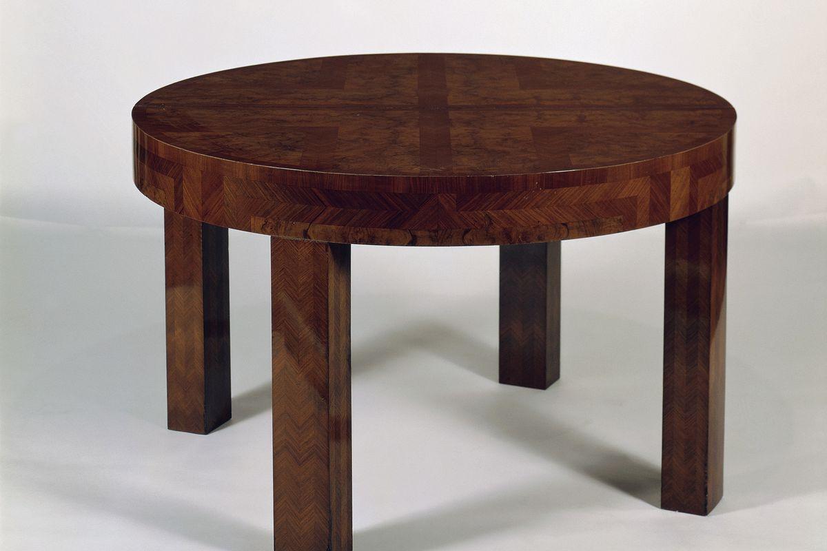 Extendible round walnut veneered table