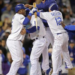 Los Angeles Dodgers' Mark Ellis, second from left, celebrates with Juan Uribe, left, Clayton Kershaw, second from right and Justin Sellers after scoring on a walk to win the game during the ninth inning of their baseball game, Friday, April 13, 2012, in Los Angeles.