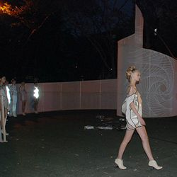 A model walks, with the threeASFOUR set behind her.