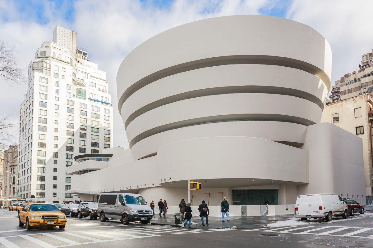 The exterior of the Guggenheim in New York City. The facade, designed by Frank Lloyd Wright, is white and curved.