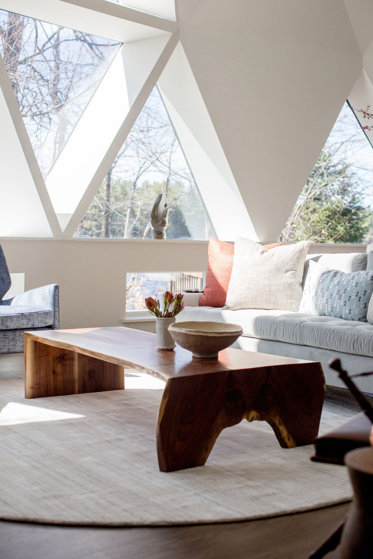 Living room with a gray couch and wooden coffee table in front of triangular windows.