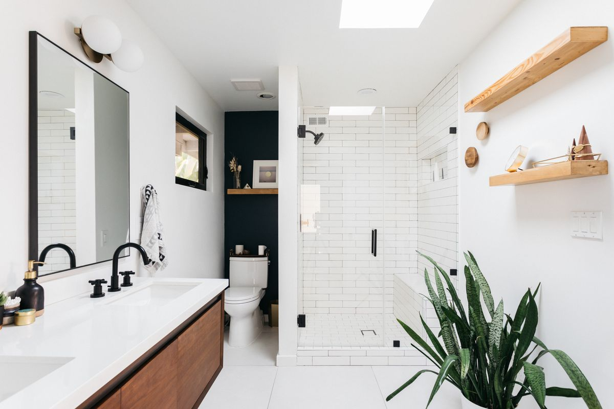 A bright bathroom with a skylight and white tile in the shower.