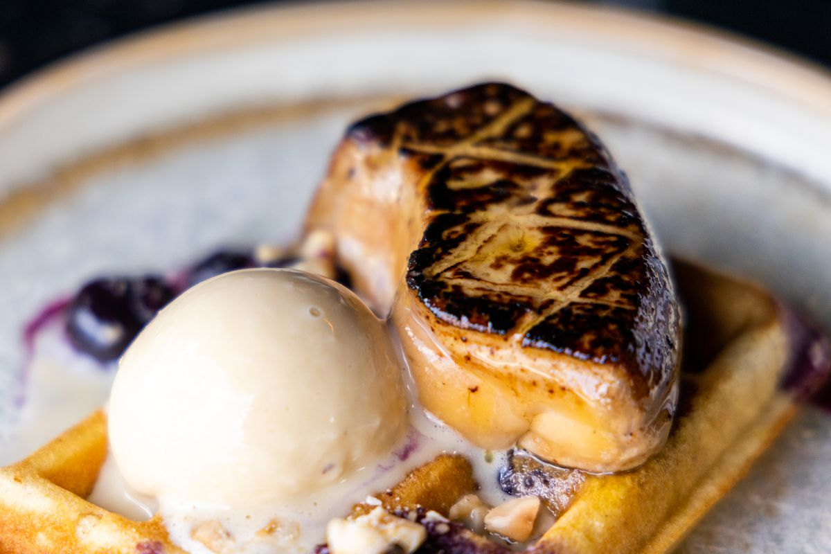 A photo of the new seared foie geas dish at Café Marmotte with the seared foie gras sitting next to a scoop of foie gras ice cream on a Huckleberry waffle