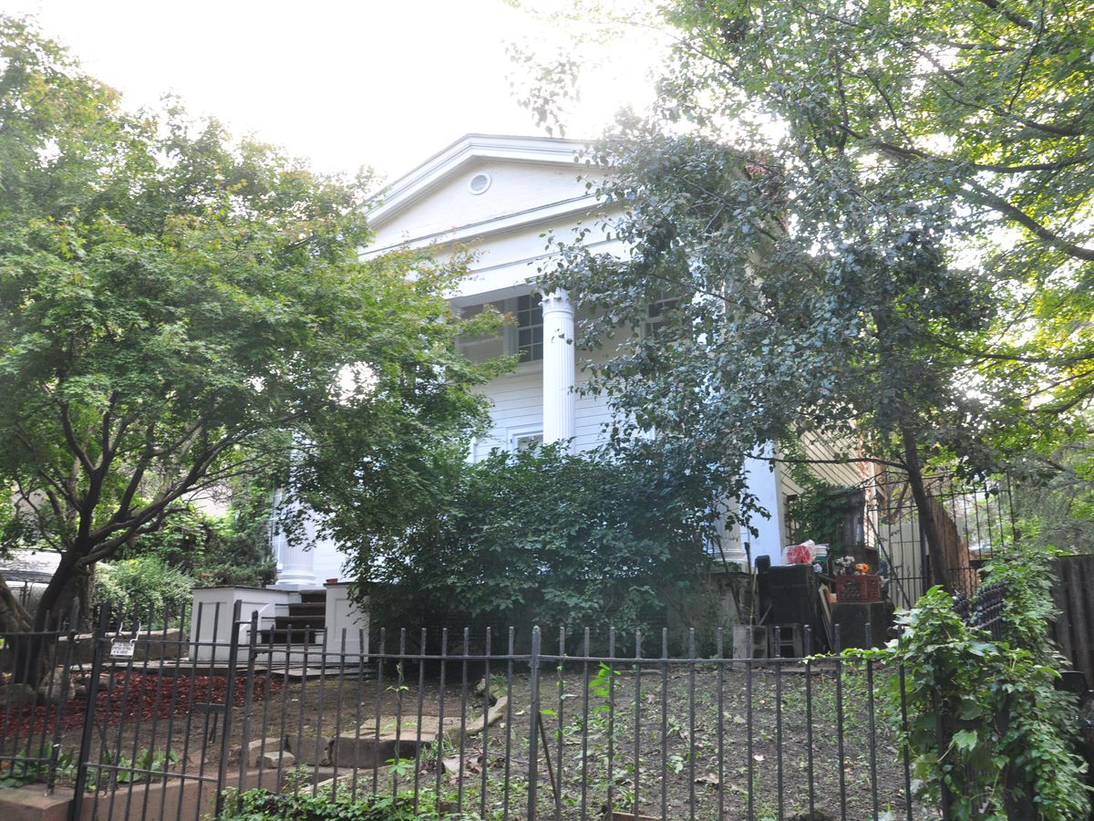 The exterior of the Lefferts-Laidlaw House in Brooklyn. The facade is white with columns. There are trees and shrubbery surrounding the house.