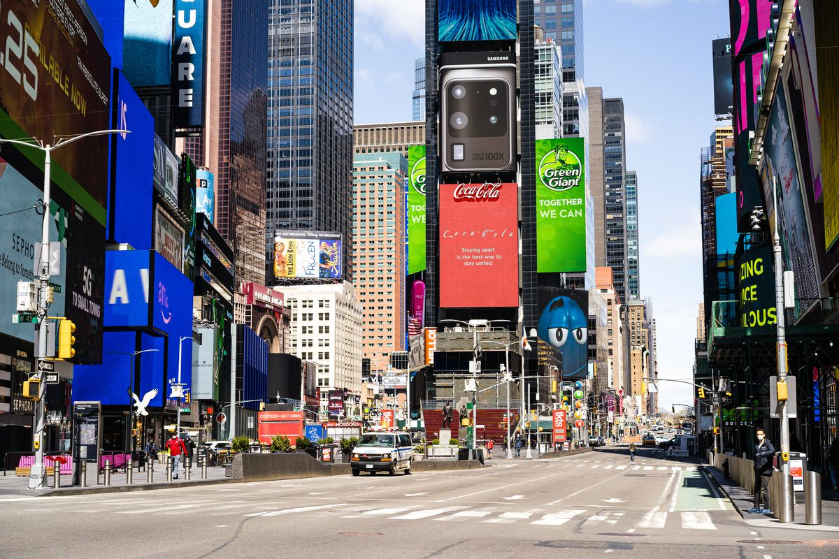 An empty scene in Times Square with large billboards in the background and no cars on the road