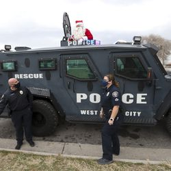 Santa waves as he rides in an armored West Valley police vehicle during the department's Giving Tree event in West Valley City on Tuesday, Dec. 22, 2020. The program provided gifts for 159 children from 51 low-income families in the city that were delivered to their homes by police officers. Each child started with a list of needed items and holiday wishes. Santa's helpers from the police department, local businesses and the community then worked hard to fulfill the wishes.
