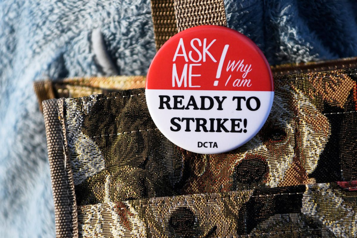 """Denver teacher Kimberly Duran wears a button that says, """"Ask me why I am ready to strike."""""""