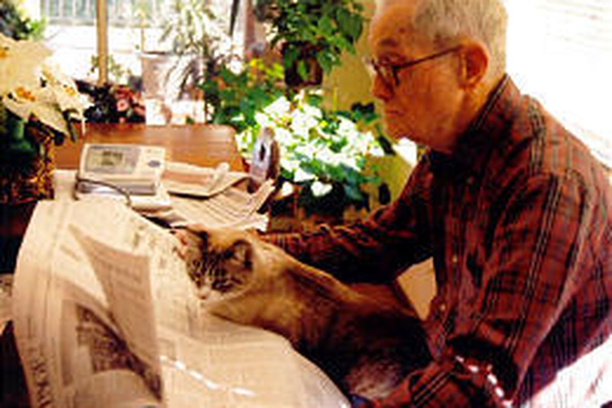 """""""Daddy Forrest"""" (Forrest Hooker) and T.C. (The Cat) read the paper in Bandera, Texas."""