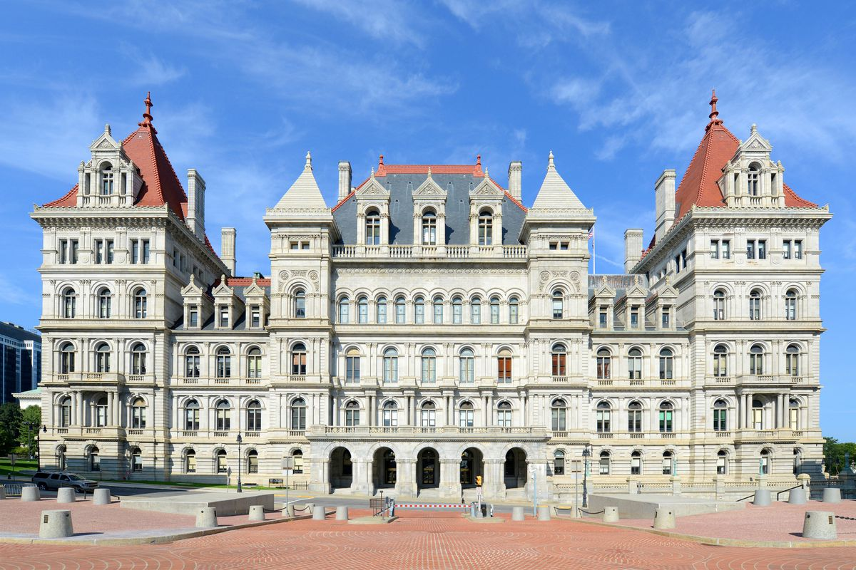 The exterior of the New York State Capitol. The building facade is white. There is an orange and dark grey roof with towers. There are many windows.